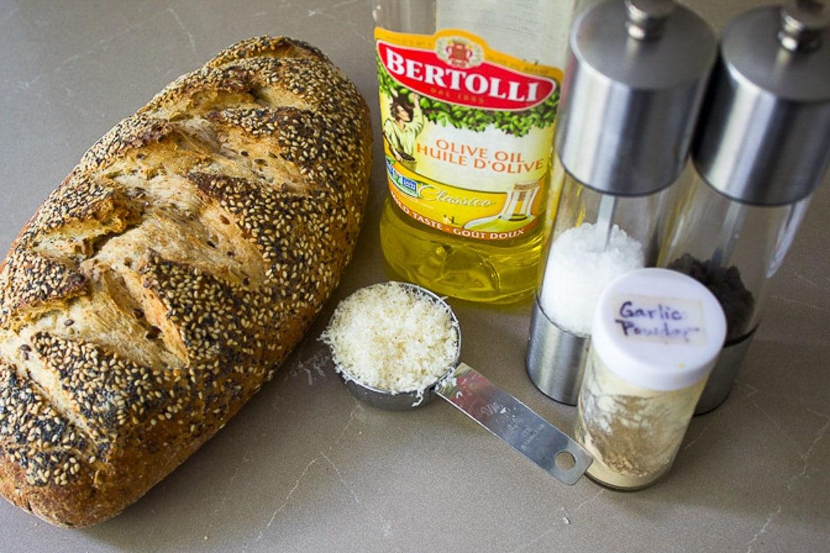 loaf of bread, olive oil, Parmesan, salt, garlic powder