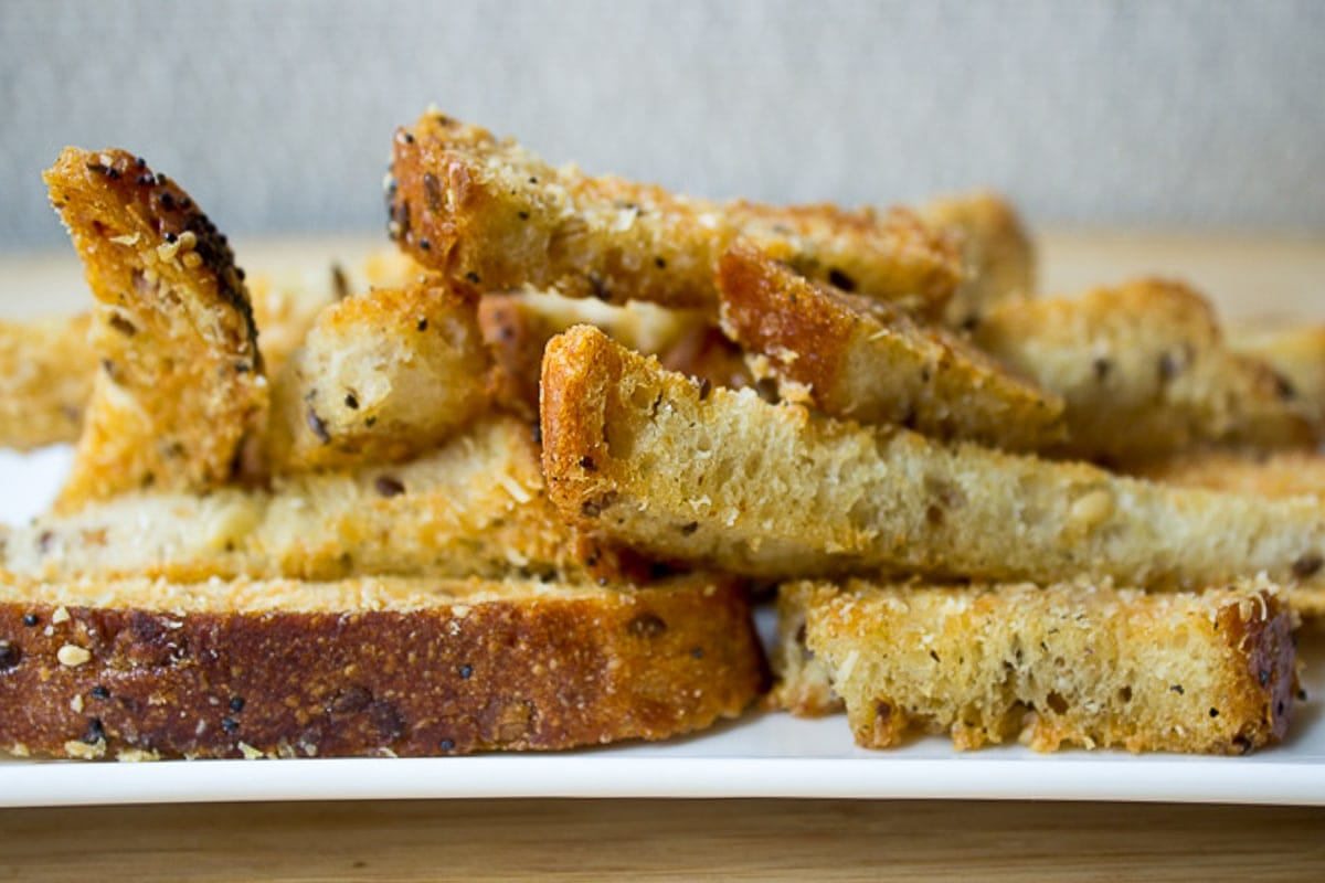 parmesan bread sticks piled on plate