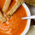 Homemade creamy tomato soup with parmesan croutons in soup p