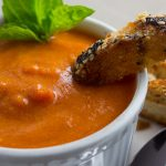 Creamy Tomato Soup in small bowl with Cheese Croutons dunked into it