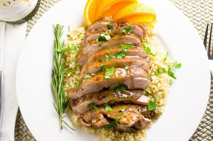 sliced boneless Turkey thighs on plate over quinoa with glaze f