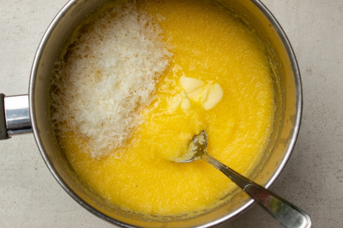 cooked polenta in pot with cheese and butter