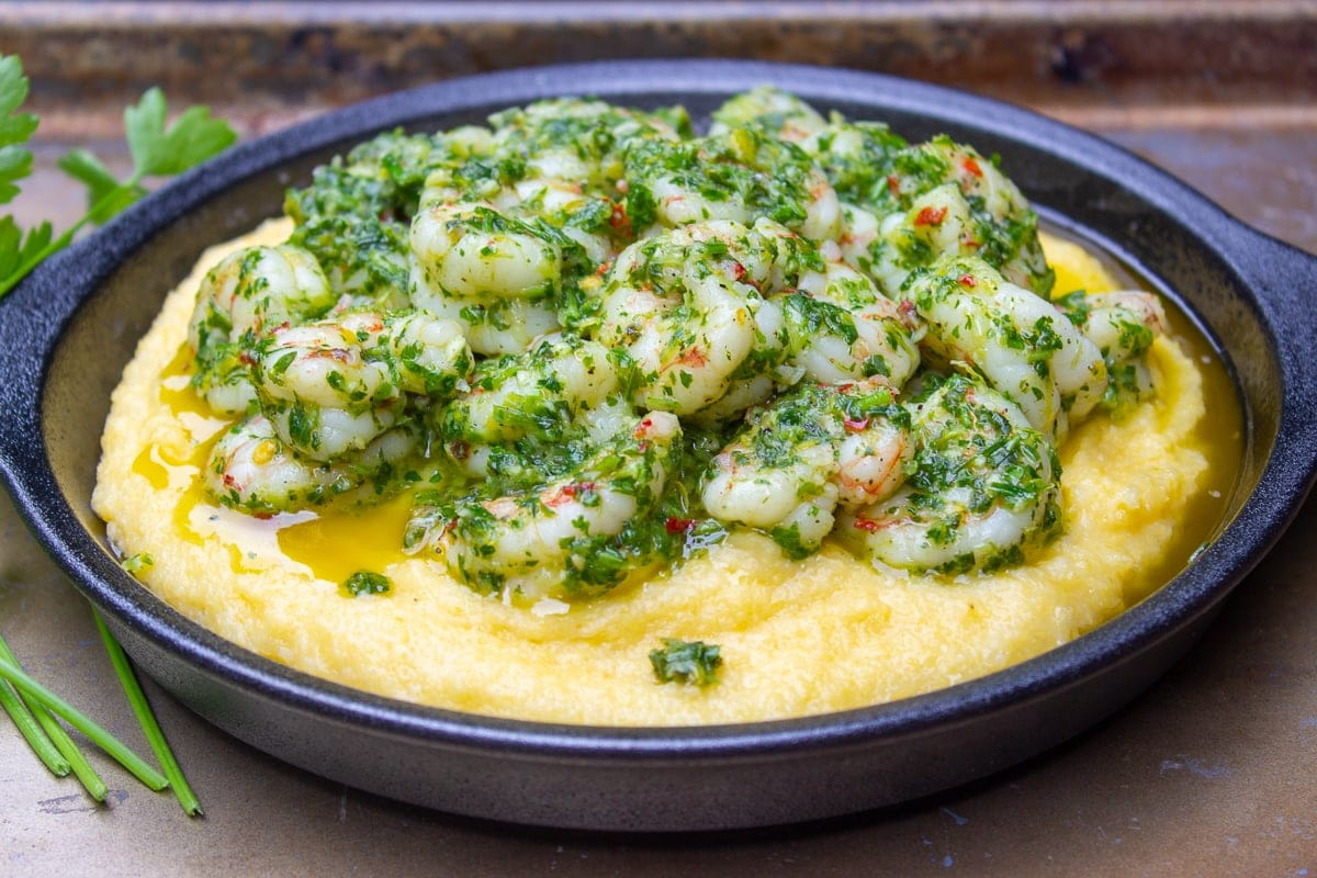 polenta on plate topped with herb shrimp