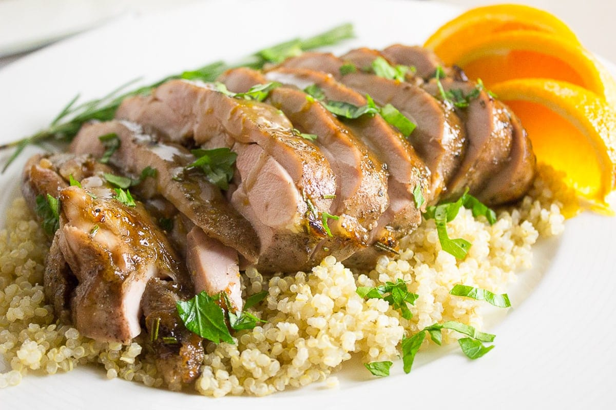 sliced sous vide turkey thighs over quinoa on plate with orange slices 2