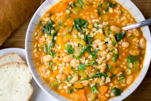 Vegetable Bean and Barley Soup in bowl with bread and butter f