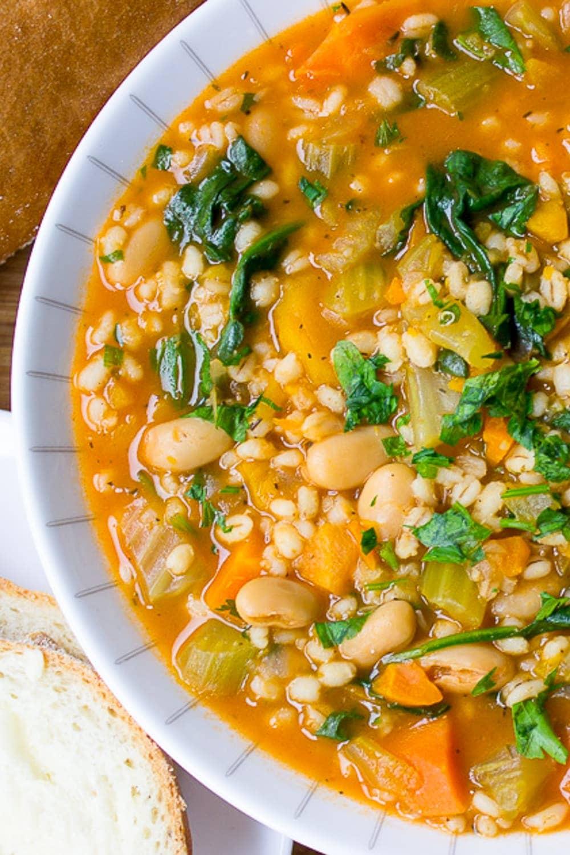 bowl of vegetable barley soup beside bread p