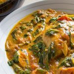 Coconut Curry Salmon with spinach and tomato served in bowl