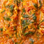 poached salmon in coconut curry sauce in pan p