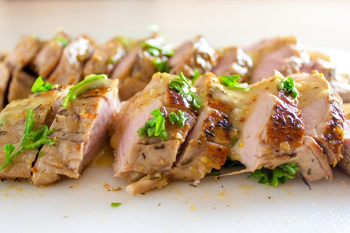 sliced pork tenderloin on cutting board 1
