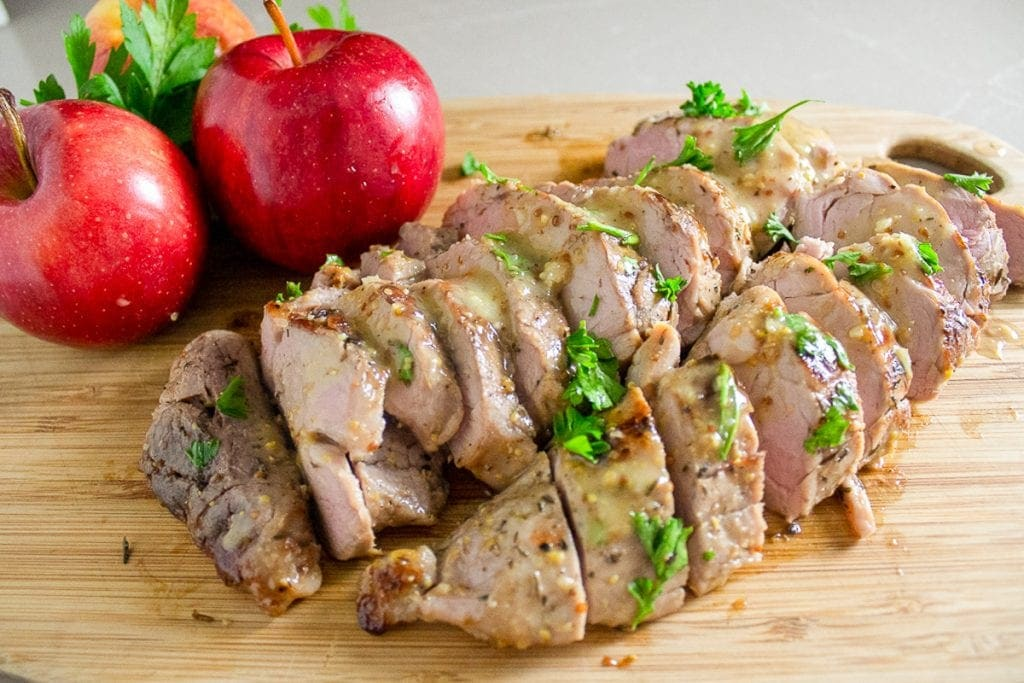 sliced sous vide maple mustard pork tenderloin with apples on cutting board f