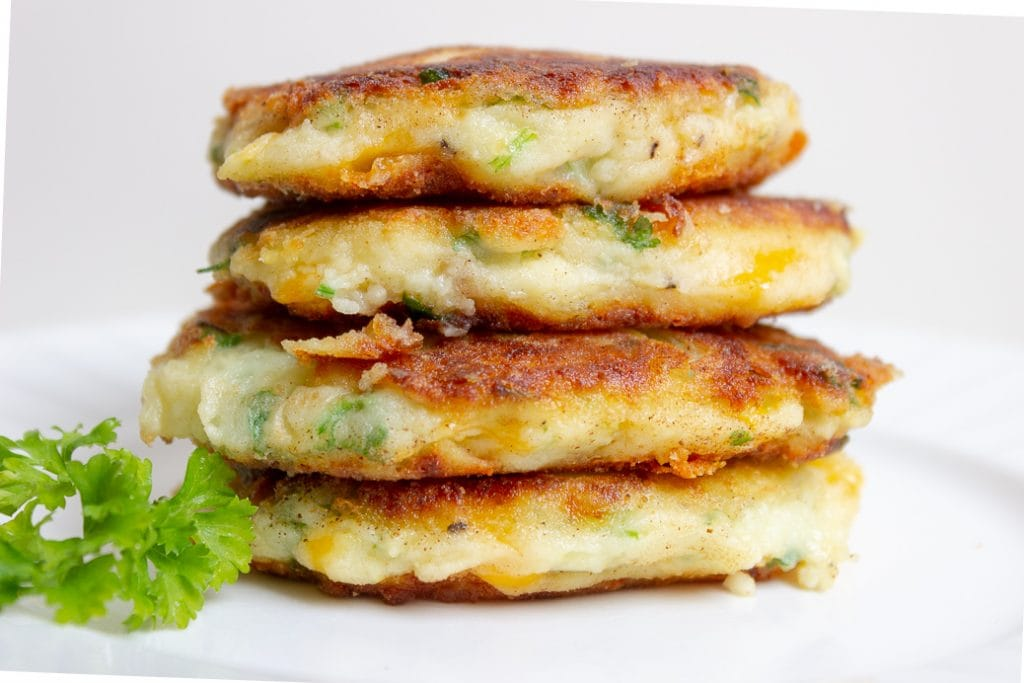 4 mashed potato pancakes (latkes) stacked on plate