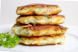 4 mashed potato pancakes (latkes) stacked on plate