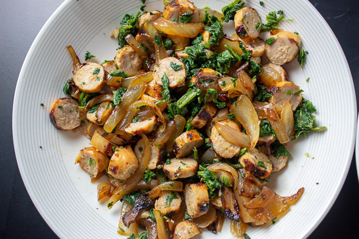 cooked onions, spinach and sausages in bowl