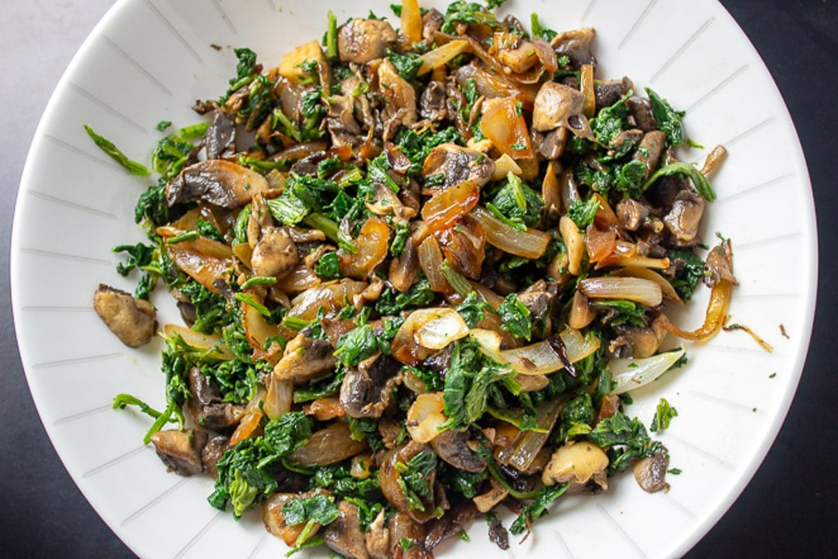cooked spinach, mushrooms and onions in bowl