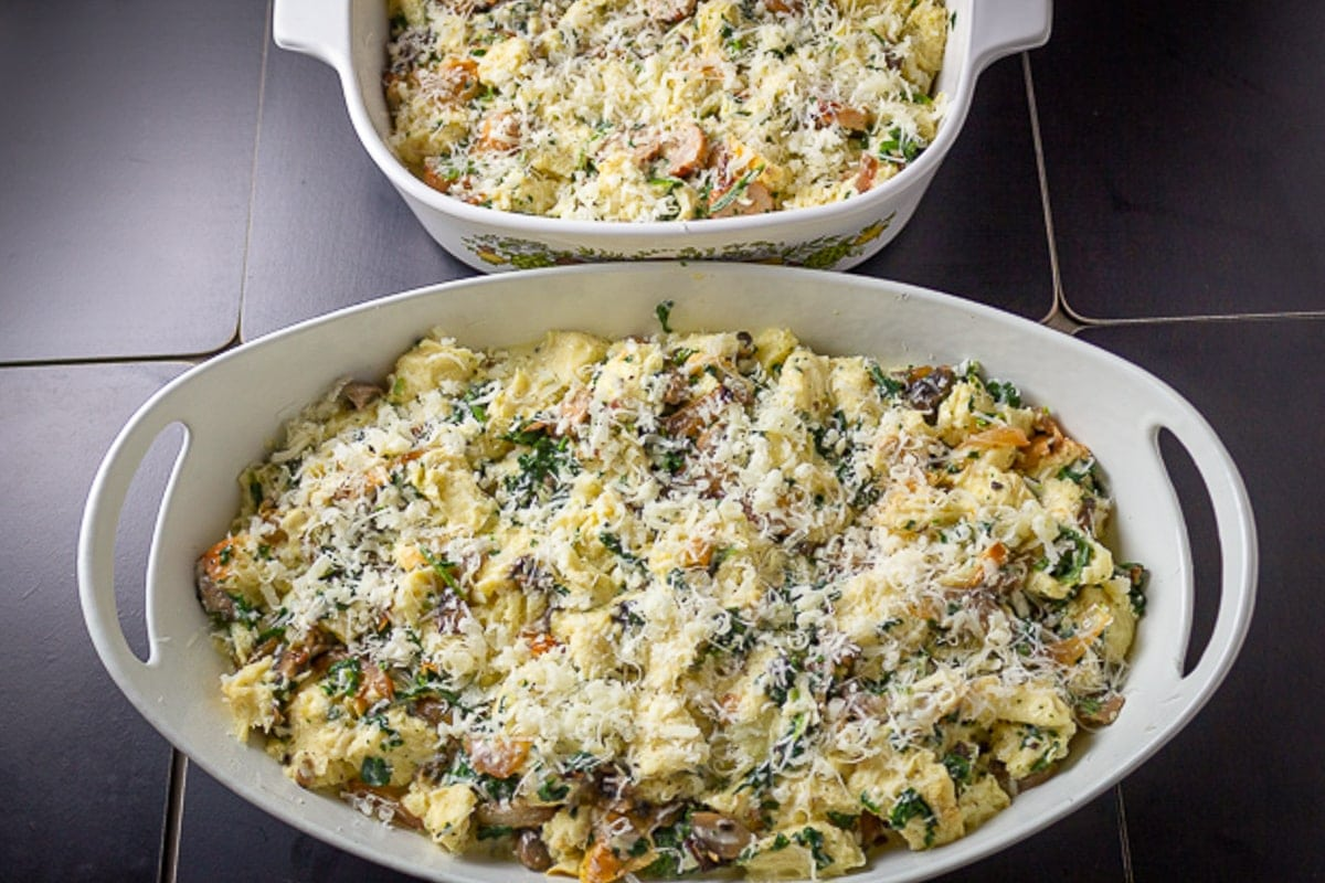 strata mixture in 2 casserole dishes with grated cheese on top