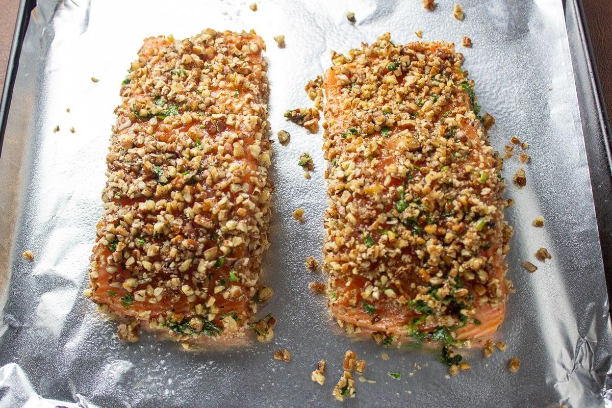 Pecan crusted salmon on pan ready to bake