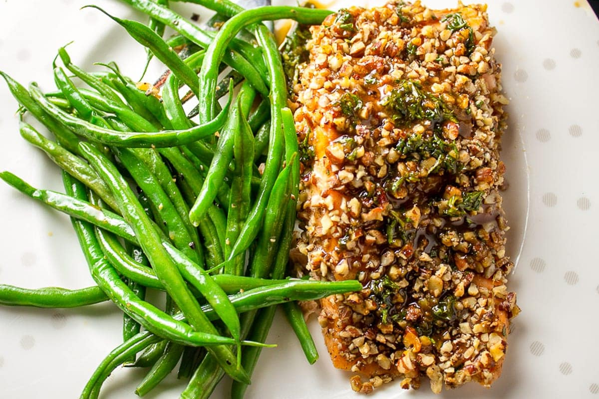 Pecan crusted salmon filet on plate with beans