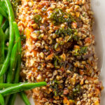 Pecan crusted salmon filet on plate with beans p