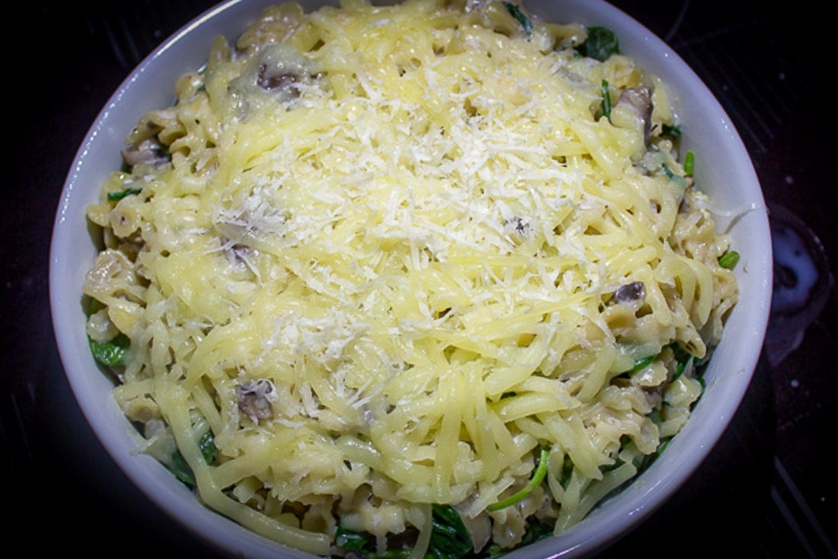 Mushroom Spinach Pasta poured into baking dish with cheese on top