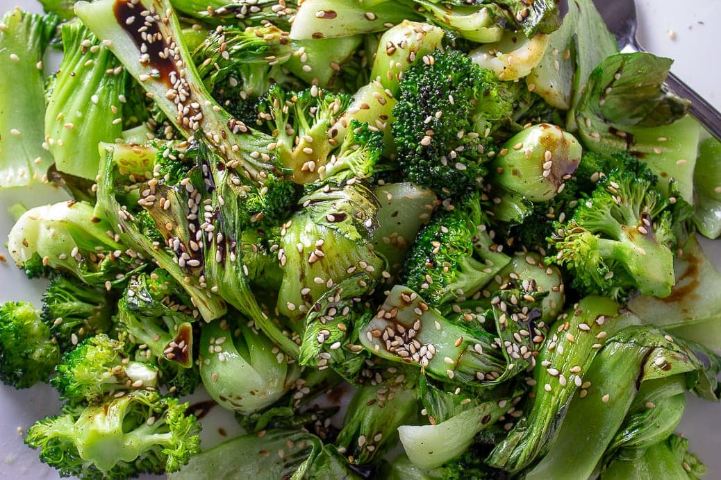 close up of roasted bok choy and broccoli with sesame seeds on plate