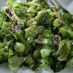 Roasted Bok Choy and Broccoli on plate drizzled with balsamic reduction and sesame seeds
