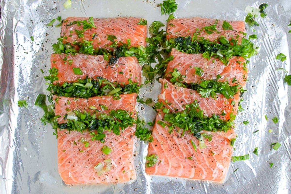 two raw salmon fillets stuffed with herbs