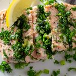 fillet of oasted Salmon Stuffed With Herbs on plate with lemon wedge p