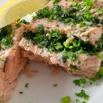 cut open fillet of oasted Salmon Stuffed With Herbs on plate with lemon wedge p