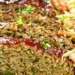 sliced chicken meatloaf on platter with coleslaw