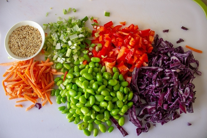 chopped purple cabbage, carrots, red pepper, green onion and sesame seeds on cutting board