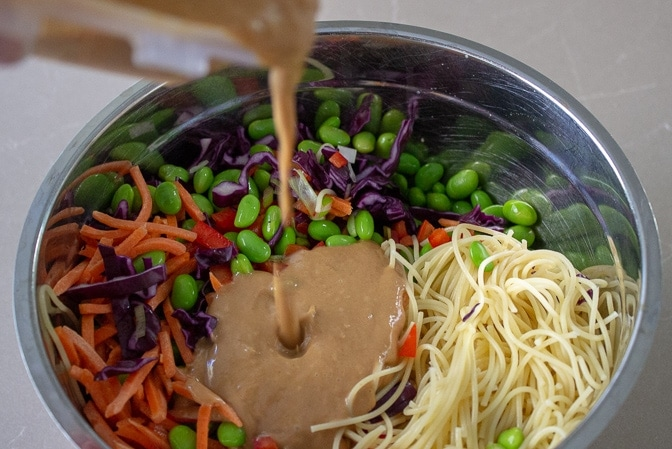 pouring peanut sauce over noodles and vegetables in bowl