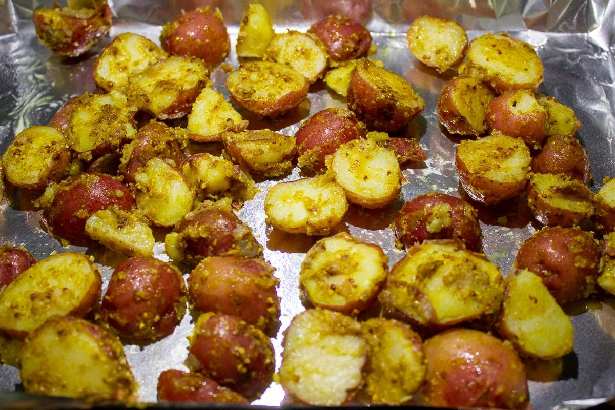 boiled potatoes mixed with spices on pan