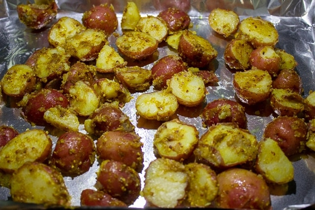 boiled potatoes mixed with indian seasonings on pan ready to roast