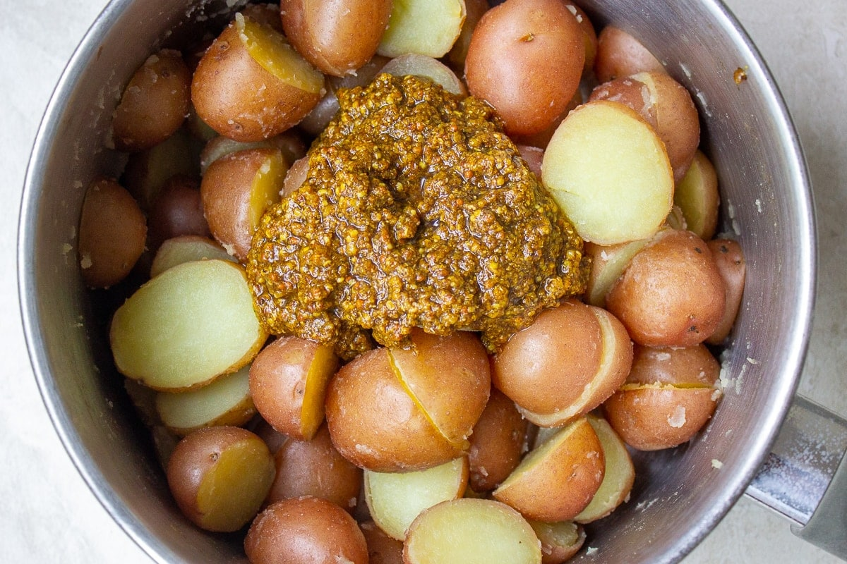 spice mix added to boiled potatoes in pot