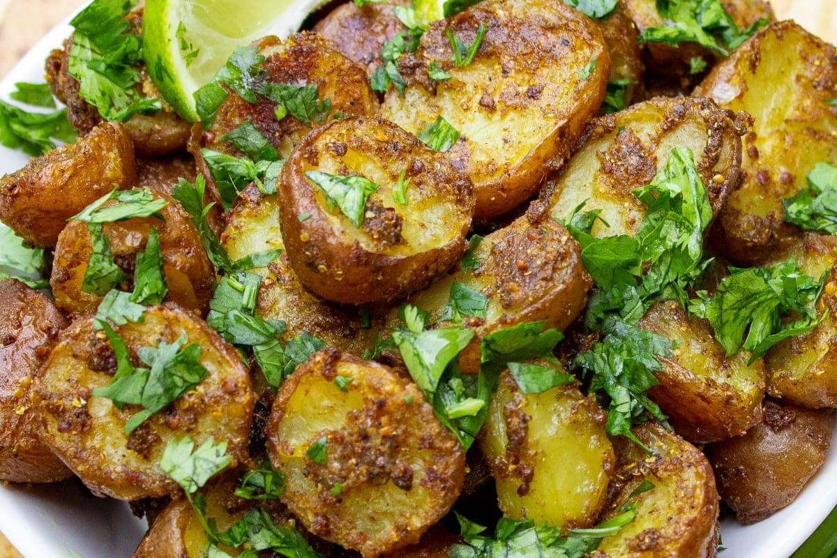bowl of indian potatoes with lime wedges