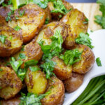 bowl of indian potatoes with lime wedges p4