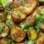 bowl of indian potatoes with lime wedges p5