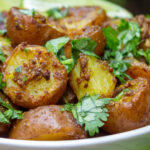 bowl of indian potatoes with lime wedges p6