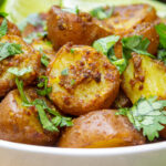 bowl of indian potatoes with lime wedges p7