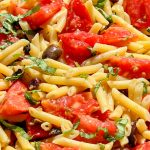 Fresh tomato pasta with lemon and olives in a serving bowl p1