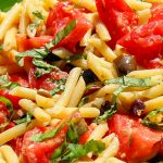 Fresh tomato pasta with lemon and olives in a serving bowl p