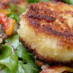 fried goat cheese round on bed of greens on plate