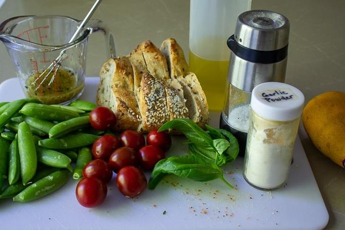 bread, olive oil, basil, cherry tomatoes, snap peas, garlic powder, salt, mango, dressing