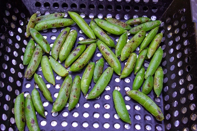 snap peas charred in grill basket