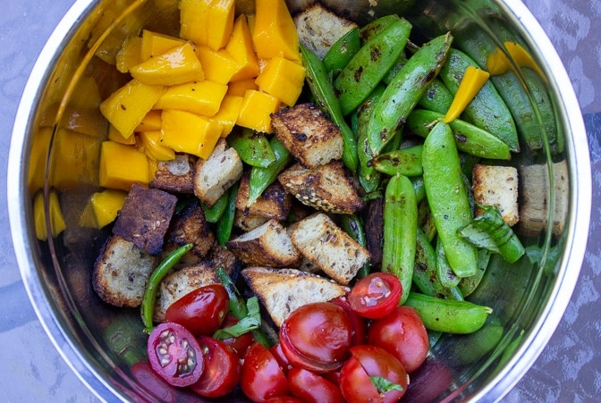 charred snap peas, tomatoes, grilled bread, mango in bowl