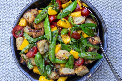 Bread salad with charred snap peas with dressing in bowl