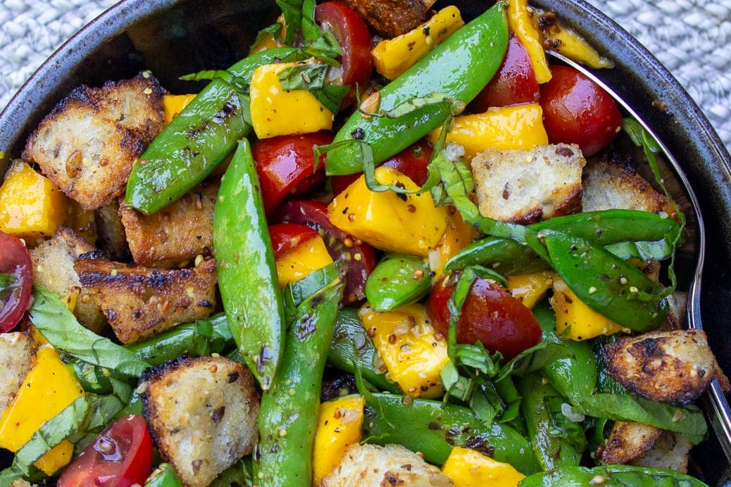Bread salad with charred snap peas close up