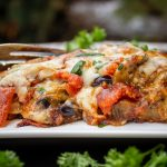 Eggplant Parmesan on plate with fork with parsley scattered around F