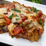 piece of Eggplant Parmesan on plate with fork p3