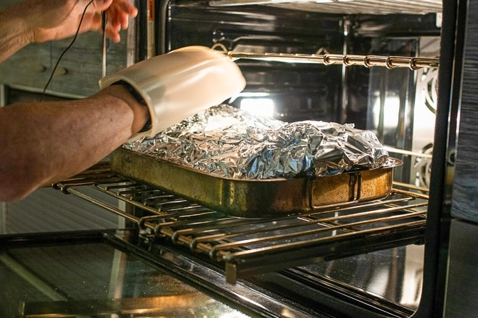 smoked brisket wrapped in foil placed in oven for final portion of cooking